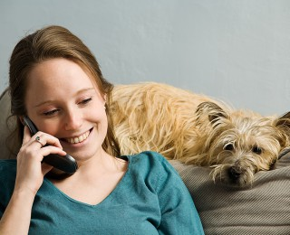 A woman keeps her dog company whilst on the phone