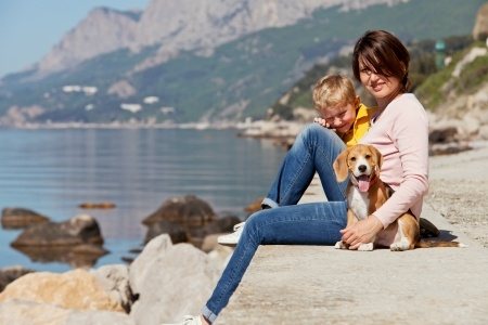 A family relax on holiday with their dog