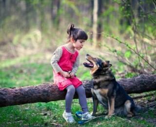 A little girl plays with her pet dog